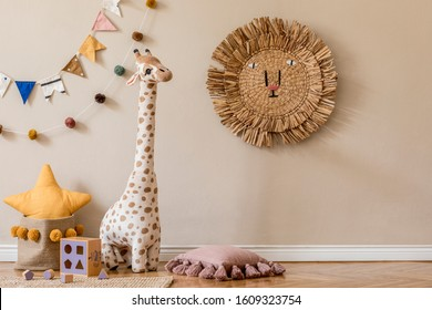 Stylish scandinavian interior of child room with natural toys, hanging decoration, pillows, plush animals, teddy bears and accessories. Beige walls. Interior design of kid room. Template. Copy space.