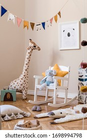 Stylish scandinavian interior of child room with natural toys, hanging decoration, design furniture, plush animals, teddy bears, mock up poster and accessories at modern home decor.