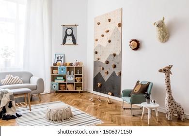 Design intérieur scandinave et élégant de chambre d'enfant avec canapé gris, mur d'escalade moderne pour enfants, mobilier design, jouets doux, ours en peluche et accessoires pour enfants mignons. Décor maison. Modèle.