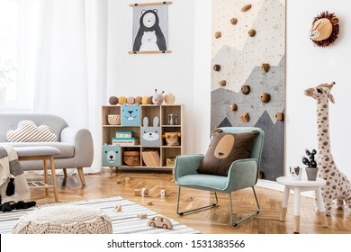 Stylish scandinavian interior design of childroom with gray sofa, modern climbing wall for kids, design furnitures, soft toys, teddy bear and cute children's accessories. Home decor. Template.