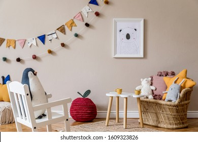 Stylish scandinavian interior of kid room with mock up poster frame, design furnitures, natural toys, hanging colorful flags, plush animal, child accessories and teddy bears. Modern home decor.