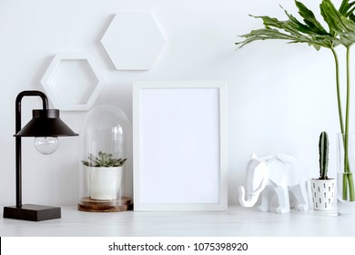 Stylish scandinavian interior with white mock up frame, lamp, cacti, leafs and white hexagone shapes. Concept of modern space.