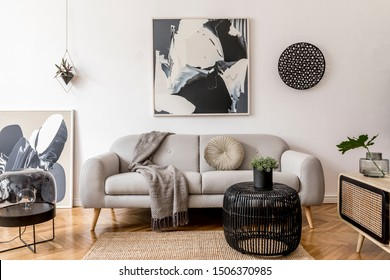 Stylish and scandinavian living room interior of modern apartment with gray sofa, pillows, plaid, plants, design wooden commode, black table, lamp, abstrac paintings on the wall.  Modern home decor.