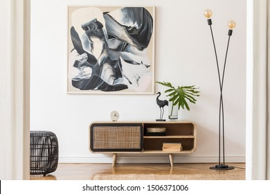 Stylish scandinavian living room interior with modern wooden commode, stylish lamps, plants, rattan basket, sculpture and elegant personal accessories. Mock up paintings on the white wall. Template.