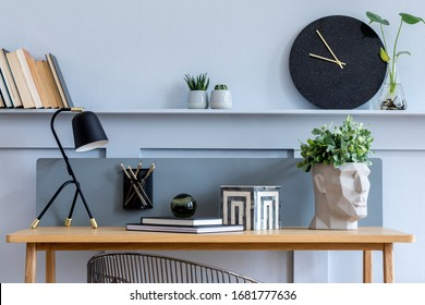 Stylish scandinavian living room interior with wooden desk, chair, wood panleing with shelf, table lamp, plants, black clock, office supplies and elegant accessories in modern home decor.