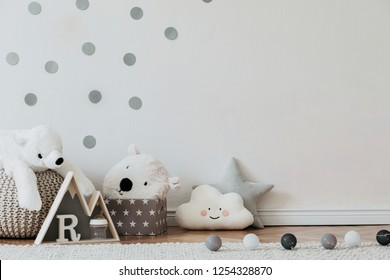 Stylish scandinavian newborn baby interior with mock up photo poster frame on the pattern wall, boxes, teddy bears and toys. White walls, wooden accessories and toys. Copy space.