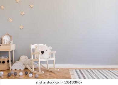 Élégante chambre de nouveau-né scandinave avec jouets, chaise pour enfants, corbeille naturelle avec ours en peluche et petite étagère. Intérieur moderne avec murs d'arrière-plan gris, parquet en bois et motif d'étoiles.