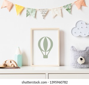 Stylish scandinavian newborn baby room with toys, teddy bear, accessories, ,cloud,colorful cotton flags and natural basket. Modern interior with mock up photo or poster frame. Real photo. Template.