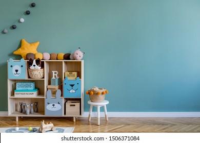 Élégante chambre de nouveau-né scandinave avec armoire en bois, jouets, chaise pour enfants, panier naturel Intérieur moderne avec murs d'arrière-plan eucalyptus, parquet en bois et balles de cottona. Décor maison.
