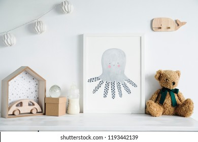 Stylish scandinavian nursery shelf with mock up photo frame, bottle with milk, teddy bears and wooden toys. Modern interior with white walls and wooden accessories..