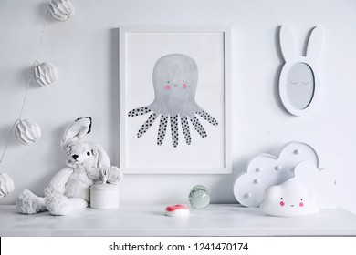 Stylish scandinavian nursery shelf with mock up photo frame, white rabbit and toys. Modern interior with white walls and wooden accessories.