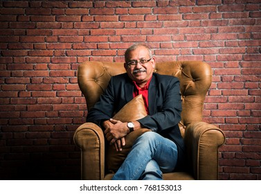 stylish senior indian man in suit sitting on sofa or wing chair. Portrait of Indian or asian millionaire or rich man