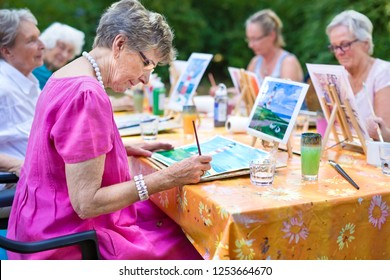 Stylish senior lady painting in art class with friends from her care home for the aged copying a painting with water colors on a canvas outdoors at a table in the garden.