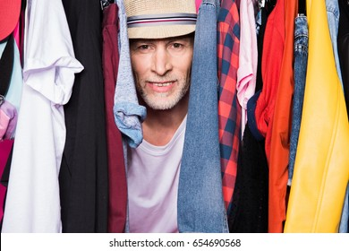 stylish senior man wearing hat and standing with different clothes on hangers and looking at camera