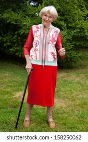 Stylish senior woman in an elegant red outfit standing on the lawn in her garden leaning on her cane giving a thumbs up gesture of success and approval