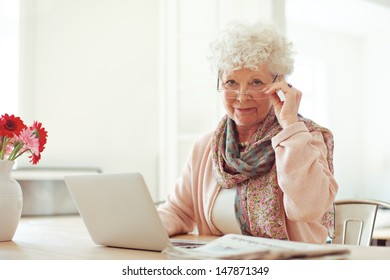 Stylish senior woman at home with laptop looking at you