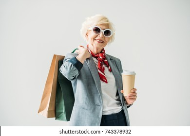 stylish senior woman in jacket and sunglasses with shopping bags and coffee, isolated on grey