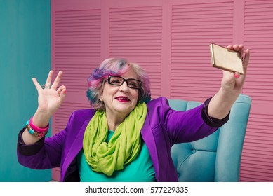 Stylish senior woman using golden smart phone and doing selfie. Retired happy modern person express herself with colorful clothes and informal hairstyle.