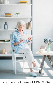 stylish senior woman using tablet at home