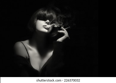 Stylish sensual young woman with trendy fringe smoking a cigarette. Short hairstyle. High fashion portrait in black and white with copy space for text.