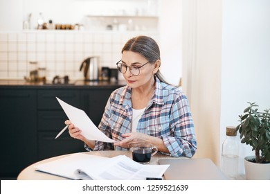 Stylish serious elderly Caucasian woman in spectacles and plaid shirt studying paper in her hand while working through papers in kitchen. Attractive mature female calculating gas and electricity bills