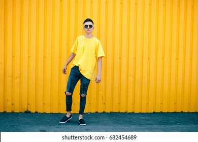 Stylish serious guy in a dirty yellow T-shirt and sunglasses and torn jeans