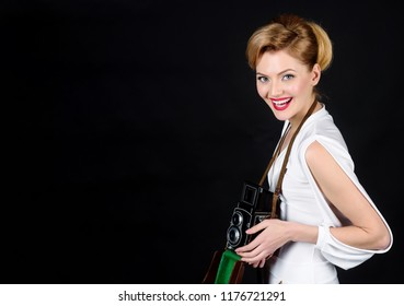 Stylish sexual lady with retro hair, makeup holds vintage retro photocamera. Family portrait, glamour, journalism. Emotions, professional make-up and hairstyle. Fashion. Retro photocamera. Copy space.