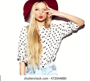 Stylish sexy beautiful young blond woman model in summer jeans hipster clothes in hat giving a kiss