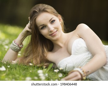 Stylish sexy beautiful young woman in a strapless dress and jewelry lying in a meadow with wildflowers smiling at the camera