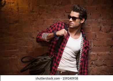 Stilvoller sexy Mann, der wegschaut. Mit Handtasche auf der Schulter