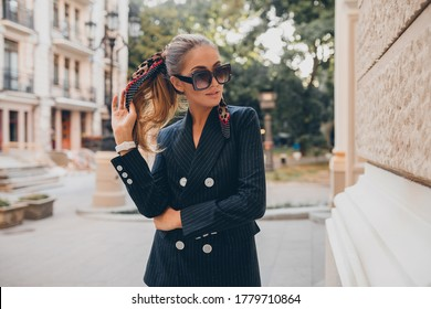 stylish sexy woman dressed in elegant tuxedo suit walking in city on summer autumn day, fashion trend, wearing sunglasses