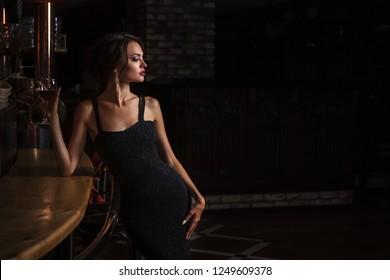 Stylish sexy woman standing near bar counter