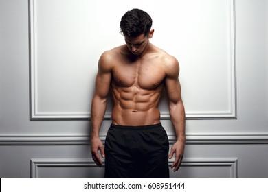 Stylish shirtless man at the white wall looking down, Horizontal studio shot.