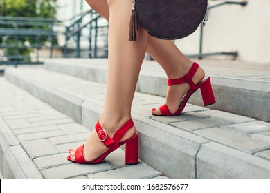 Stylish shoes and accessories. Young woman wearing fashionable red high-heeled sandals and holding handbag walking downstairs outdoors. Spring footwear