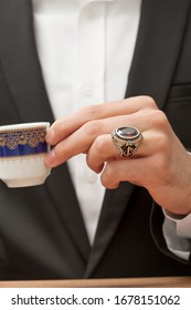 stylish silver ring on male model finger in black suit