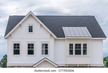 Stylish single family house facade with white vertical vinyl siding, gable with attic window and decorative brackets