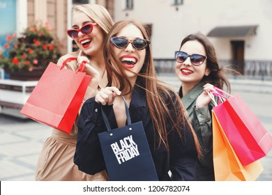 Stylish slim ladies wearing trench-coat and sunglasses walking with colorful shopping bags near the store during shopping process, concept of consumerism, sale, rich life