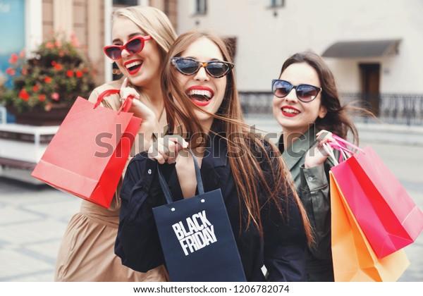 買い物の過程で、店の近くに色とりどりの買い物袋を持って歩く、トレンチコートとサングラスを着たスタイリッシュなスリムな女性、消費、販売、豊かな生活