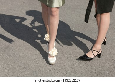 stylish slim legs and shoes of a bride with floral accessoire
