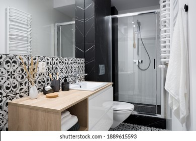 Stylish and small bathroom with decorative wall and floor tiles, big mirror and shower behind glass sliding doors