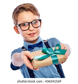 Stylish small boy in glasses giving a gift. He is smiling and looking in the camera. Isolated on a white background.