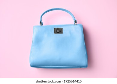 Stylish small women's bag on pink background, top view