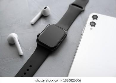 Stylish smart watch, phone and earphones on grey stone table, closeup