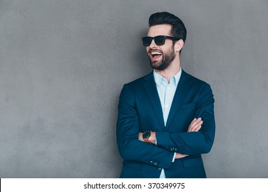 Stylish smile. Cheerful young handsome man in sunglasses keeping arms crossed and looking away with smile while standing against grey background