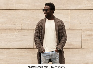 Stylish smiling african man looking away wearing brown knitted cardigan and sunglasses on city street over brick wall background