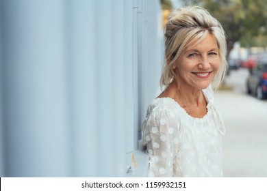 Stylish smiling blond woman in an urban street leaning against a wall turning to look at the camera with copy space