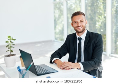 Stylish smiling businessman in elegant suit sitting at his desk in a bright modern office. business success concept