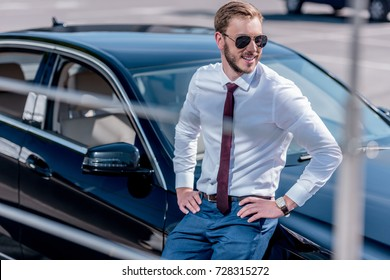 stylish smiling businessman in sunglasses leaning on car