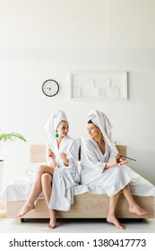 stylish smiling women in bathrobes and jewelry, with towels on heads sitting on bed with nail files