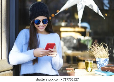 Stylish smiling young woman in cool sunglasses chatting with friends on mobile phone sitting outdoors.Cheerful hipster girl in hat messaging online in social networks on modern smartphone device
